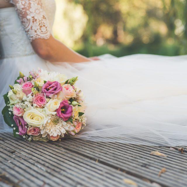 Foto einer sitzenden Braut mit Blumenstrauß