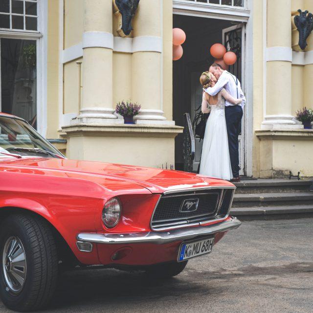 Ein sich küssendes Brautpaar neben einem roten Ford Mustang
